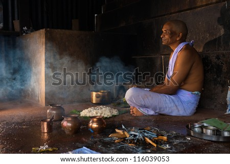 GOKARNA, INDIA - MARCH 3: A hindu man prays and offers food and gifts to a recently deceased relative in Gokarna, an important pilgrimage site, on March 3, 2009 in Gokarna, India - stock photo