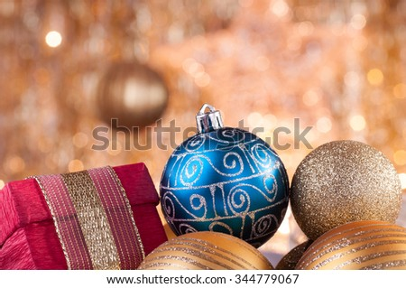 gold and blue christmas baubles and red box on background of defocused golden lights. - stock photo