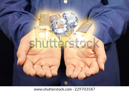 Gold and diamonds hovering above two hands. - stock photo