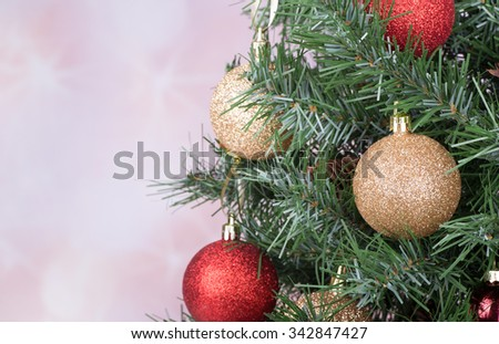 Gold and red baubles on a Christmas tree with holiday background - stock photo
