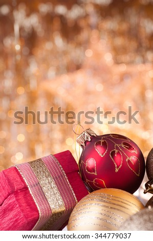 gold and red christmas baubles and red box on background of defocused golden lights. - stock photo