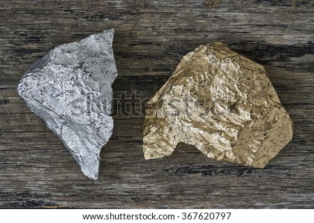 Gold and Silver ore on wood plate - stock photo