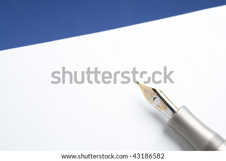 Gold and Titanium Fountain Pen on Stationery and Blue Background - stock photo