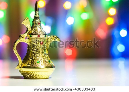 Gold  Arabic Coffee pot in colorful illuminated background. Ramadan and Eid concept  - stock photo