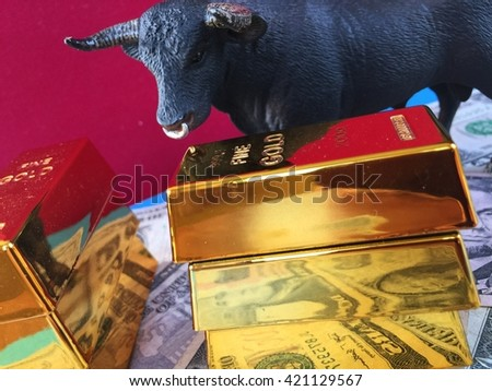 Gold bars, US dollar banknotes and bull on red background - stock photo