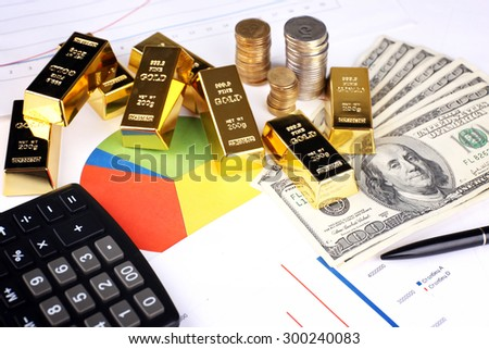 Gold bullion with money on table close up - stock photo