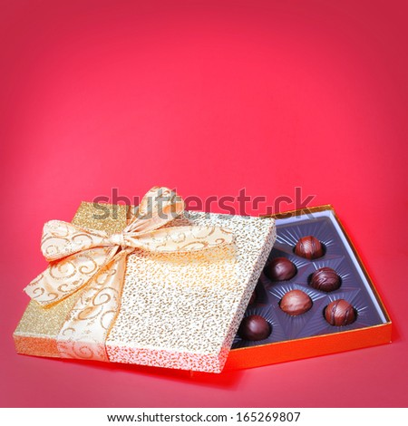 Gold Candy Box with Truffles over red background. Christmas Gift  - stock photo