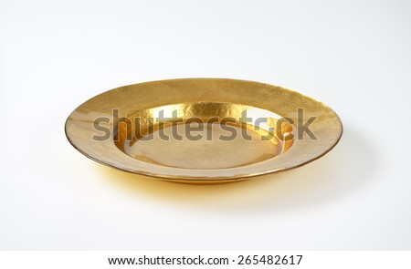Gold charger plate with wide rim - stock photo
