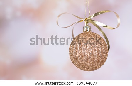 Gold Christmas ball hanging with a colorful background - stock photo