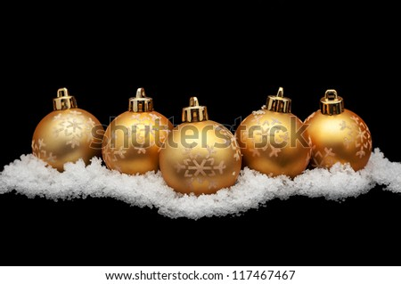 Gold christmas balls with snow isolated on black - stock photo
