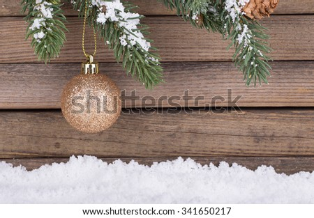Gold Christmas bauble hanging from evergreen branch with a wood background - stock photo
