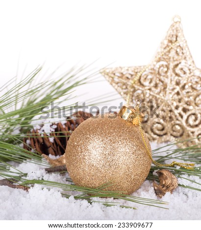 Gold Christmas bauble with pine needles and star with snow on white background - stock photo
