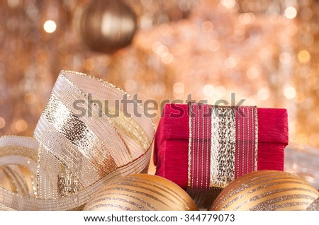 gold christmas baubles and red box on background of defocused golden lights. - stock photo