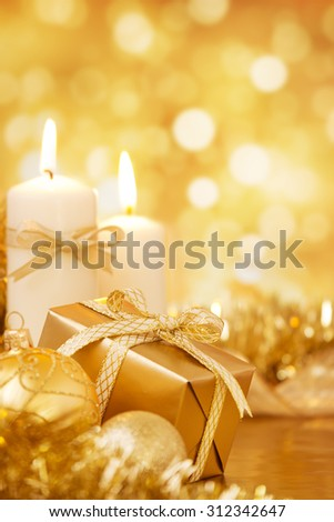 Gold Christmas baubles, candles and a gift on a bright glittering gold background. - stock photo