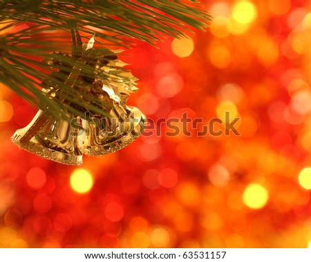 Gold Christmas bells on pine bough - stock photo