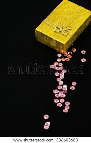 Gold christmas gift box and pink sequins on black background - stock photo