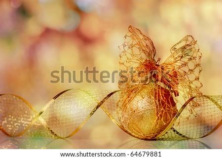 Gold Christmas ribbon ornament on background of defocused golden lights. Shallow DOF. - stock photo