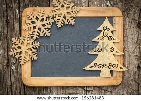Gold Christmas tree decorations on vintage wooden blackboard with copy space. Xmas holidays card - stock photo