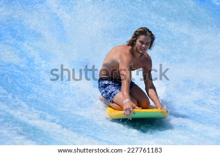 GOLD COAST OCT 29 2014: Young man ride a surfing board on FlowRider. It is a water park attraction that simulate the riding of waves in the ocean - stock photo