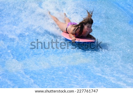GOLD COAST OCT 29 2014: Young woman ride a surfing board on FlowRider. It is a water park attraction that simulate the riding of waves in the ocean - stock photo