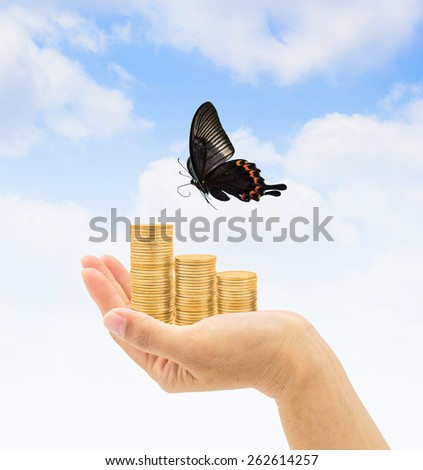 Gold coin stacks on a hand with flying butterfly freely reaching the sky with clouds: Freedom in financial management concept - stock photo