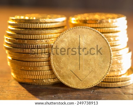 Gold coin with arrow down - stock photo