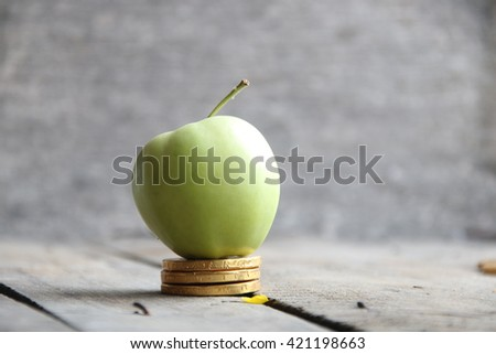 gold coins and apple - stock photo