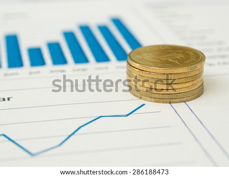 Gold coins and financial reports.  investment concept.  selective focus. - stock photo
