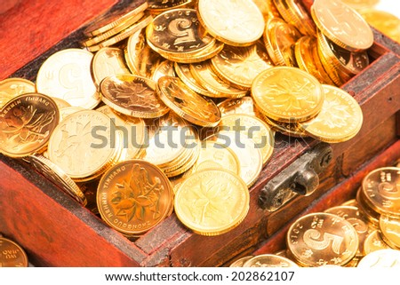 gold coins in wooden box  - stock photo