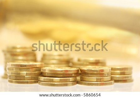 Gold coins, with golden reflection in the background.  Very shallow DOF. - stock photo