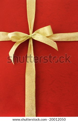 Gold color bow ribbon on red background - stock photo