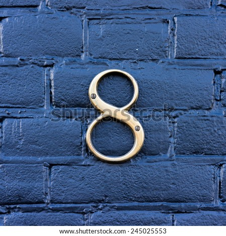 Gold colored house number eight - stock photo