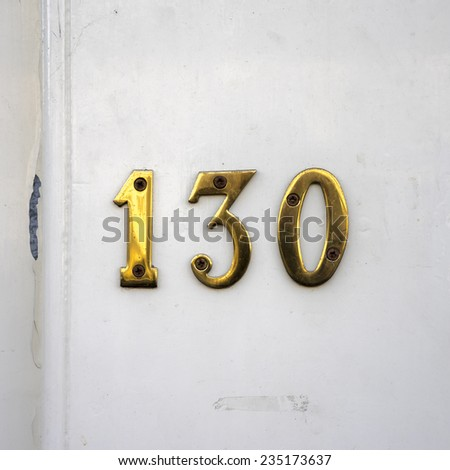 Gold colored house number one hundred and thirty - stock photo
