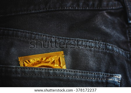 gold condom pack in back pocket jeans,abortion concept. - stock photo
