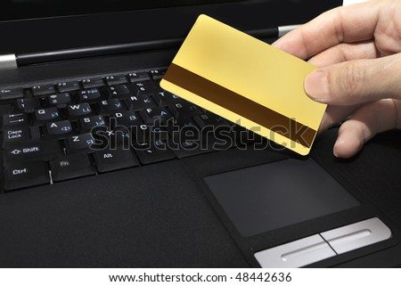 gold credit card on the background of a laptop - stock photo