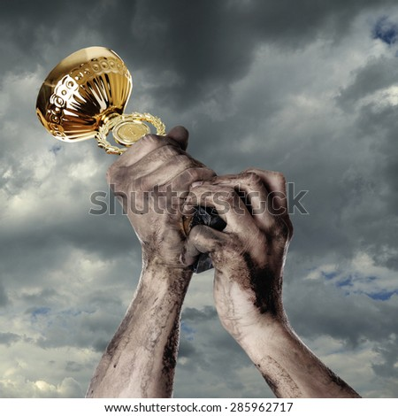 Gold cup in dirty hands on sky background - stock photo