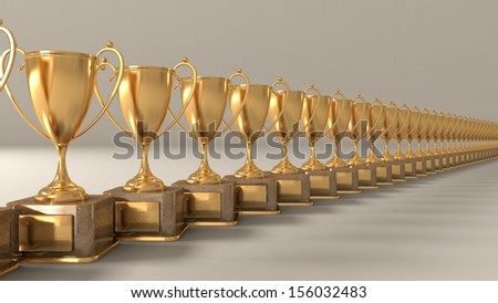 gold cups on a support with the handles, standing in an equal row award for winners - stock photo