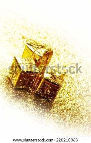 Gold decorative boxes with holiday gifts on abstract gold background with white copy space - stock photo