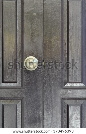 Gold door knob on brown wood door. - stock photo