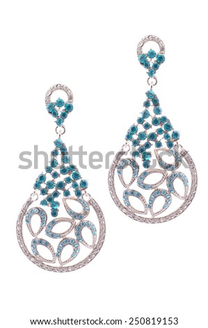 Gold earrings inlaid with precious stones on a white background - stock photo