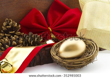 Gold egg in twig nest with holiday red bow and pine cones in wood box offers a rustic, homestyle view of financial savings and investment.  Gift of start or addition to portfolio is concept.  - stock photo