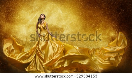 Gold Fashion Model Dress, Woman In Golden Silk Gown Flowing Fabric, Beautiful Girl on Stars Sky looking up - stock photo
