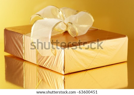 Gold foil gift with golden bow on golden background with reflection. - stock photo
