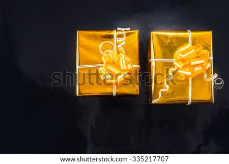 Gold foil wrapped Christmas gifts with decorative golden ribbons and bows standing side by side on a black background with copyspace for your greeting - stock photo