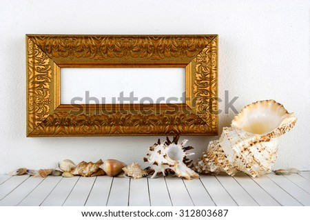 Gold frame on a wall with sea shells - stock photo