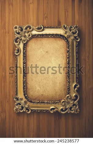 Gold frame with old paper on wood background - stock photo