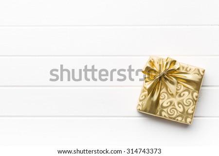 gold gift box on white table - stock photo
