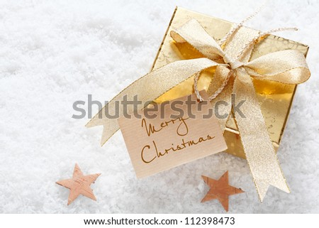 Gold gift with a decorative ribbon and Merry Christmas tag nestling on fresh snow with stars and copyspace - stock photo