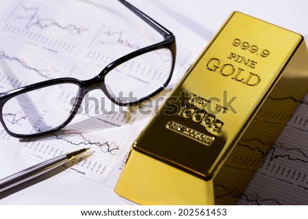 Gold ingot resting on a stocks and shares graph representing  - stock photo