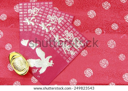 Gold Ingots and Red Packet on  fragment of red chinese silk for background Chinese New Year - stock photo